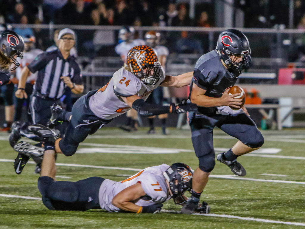 Camas quarterback Jack Colletto (9) escapes the grasp of Battle Ground defenders Bailey Buckner (24) and Spencer Matz (77). Photo by Mike Schultz.