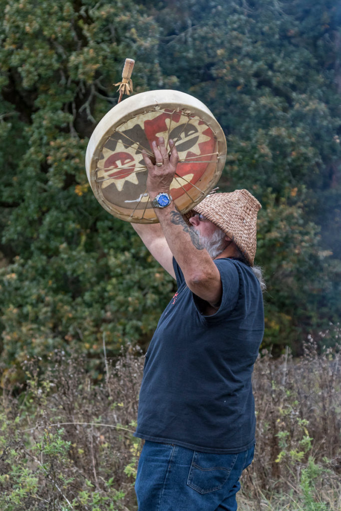 Chinook Tribal Vice Chairman, Sam Robinson playing a drum during the blessing of food and friendship before the traditional salmon bake at the Cathlapotle Plankhouse, Sun., Oct. 2 at the Carty Unit of the Ridgefield National Wildlife Refuge during Bird Fest. Photo by Mike Schultz.