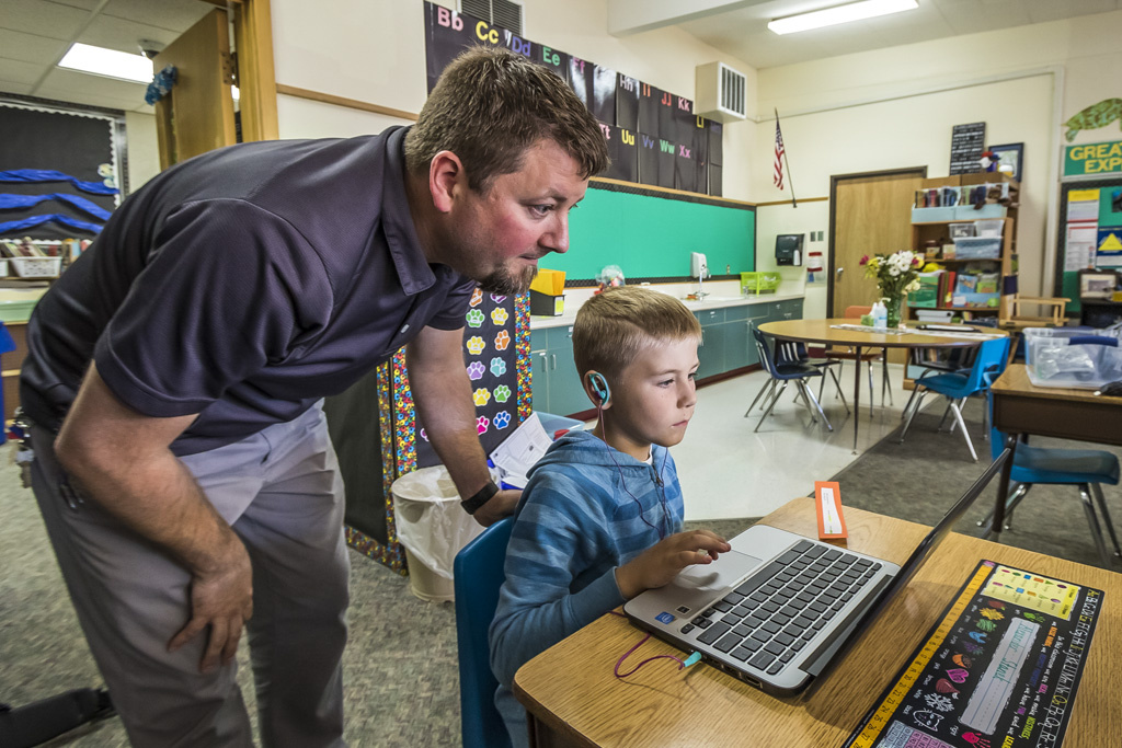 Damen Hermans, assistant principal at Glenwood Heights Primary School, assists second-grade student Alexander Stanek with logging onto the computer. Alexander is a second grader in Shannon Brown's class. Photo by Mike Schultz