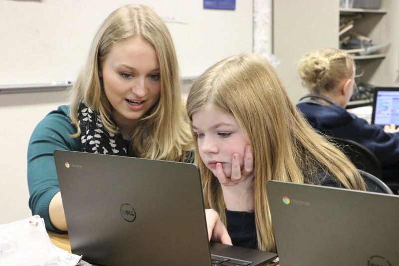 CAM Academy teacher Alexis Scott assists student Emersyn Christenson on a computer at the school. Photo courtesy of Battle Ground Public Schools