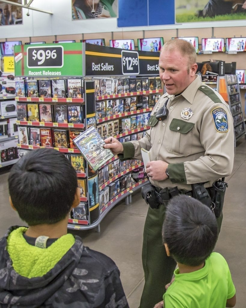 Brandon Chamberlain, of the Washington Department of Fish and Wildlife, helps a pair of kids with their shopping Saturday at the Woodland Walmart. Photo by Mike Schultz