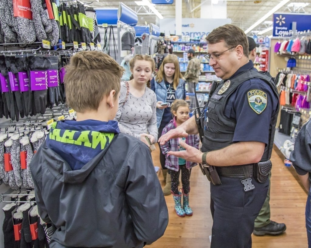 Brent Murray, of the Woodland Police Department, listens intently to his youngster Saturday at the Shop With a Cop event at the Woodland Walmart. Photo by Mike Schultz