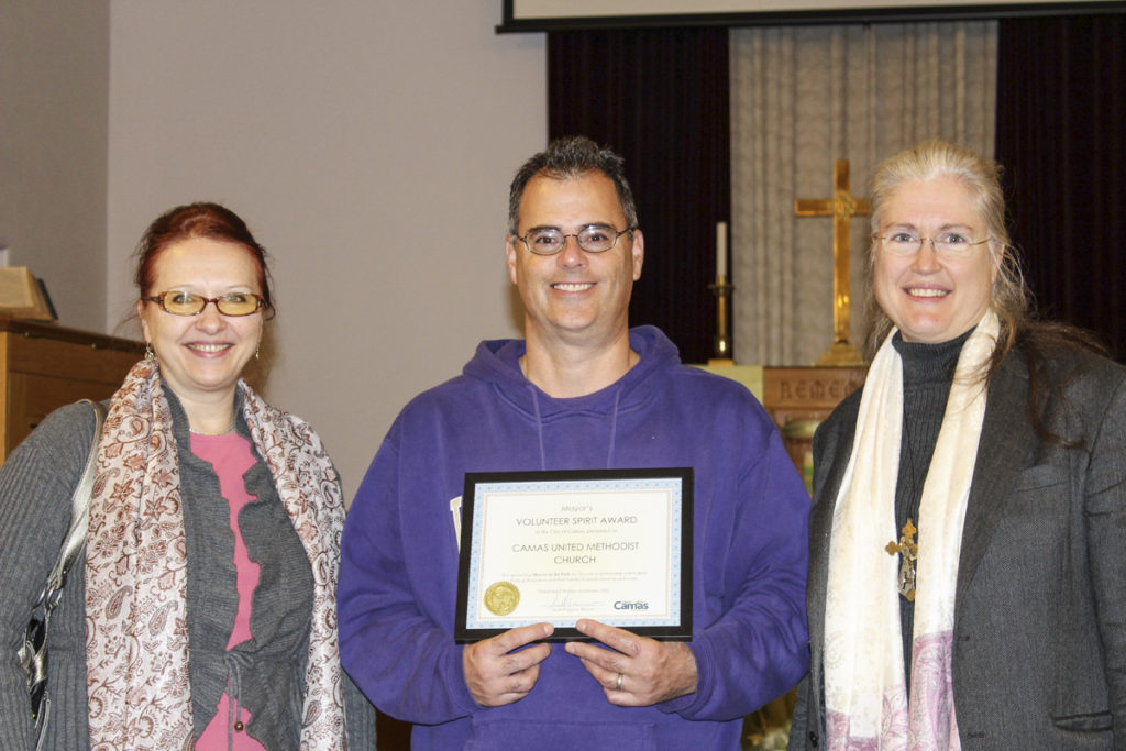 Rev. Richenda Fairhurst (right) says she's honored that her church, the Camas United Methodist Church, recently received the Camas Mayor's Volunteer Spirit Award for its sponsorship of the city's Movies in the Park event for the past 10 years. Here, Fairhurst is pictured with congregants Byron Boyd (center, holding volunteer spirit award) and Dr. Tatiana Kolchanova (left) in the church's sanctuary. Photo by Kelly Moyer