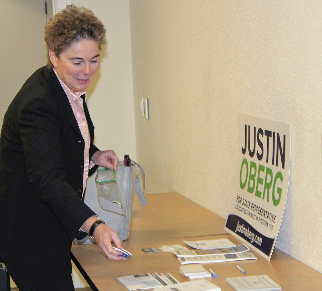 Vancouver Public Schools School Board Director Kathy Gillespie, places her information on a table at the Neighborhood Associations Council of Clark County's candidates forum for Legislative District 18. Gillespie is running for a seat in the state House of Representatives against current Rep. Liz Pike. Photo by Kelly Moyer