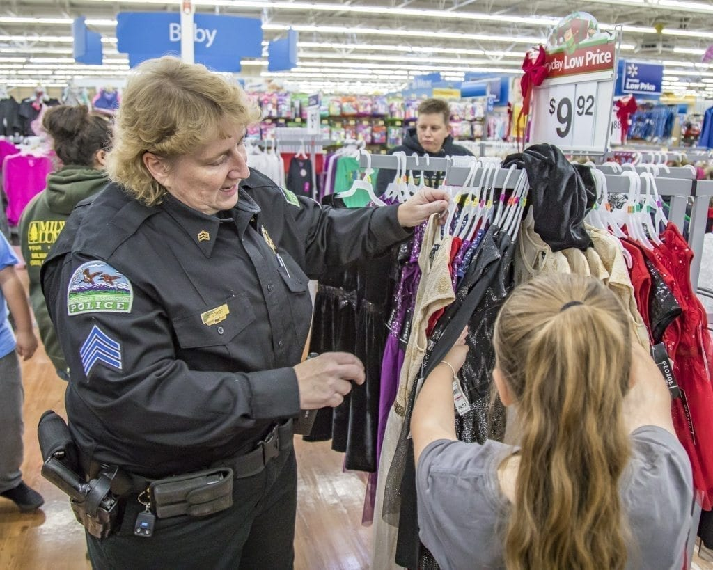 Cathy Doriot, of the Ridgefield Police Department, helps her shopper check out some clothes Saturday at the annual Shop With a Cop event at the Woodland Walmart. Photo by Mike Schultz