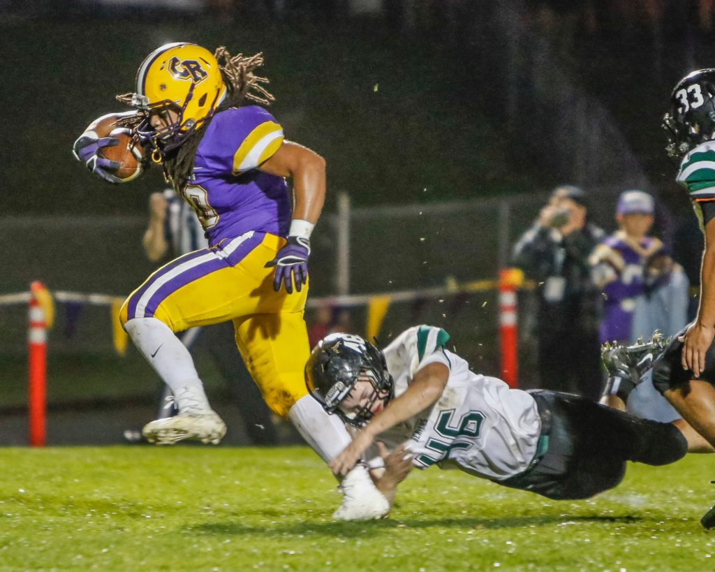 Columbia River running back Hunter Pearson (30) out steps the grasp of a Woodland defender Jack Wear (46) and races for a touchdown Friday against the Beavers. Photo by Mike Schultz.
