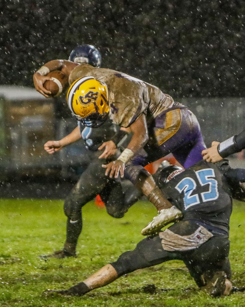 Columbia River defensive back Nathaniel Trevino (4) is tackled by Hockinson wide receiver Matt Henry (25) after making an interception. Photo by Mike Schultz.
