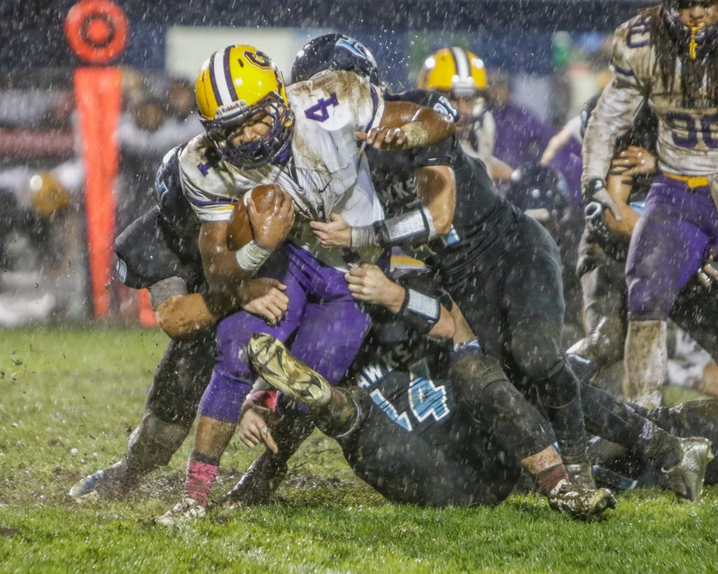 Columbia River running back Nathaniel Trevino (4) is stopped by multiple Hockinson defenders. Photo by Mike Schultz.