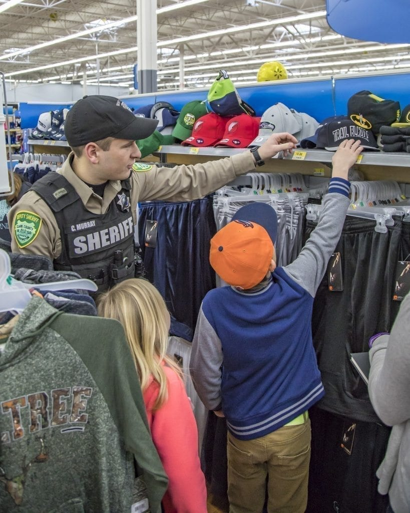 Sometimes it's nice to have someone around who can reach the top shelf, Craig Murray of the Clark County Sheriff's Office helps a youngster do just that Saturday at the Shop With a Cop event at the Woodland Walmart. Photo by Mike Schultz