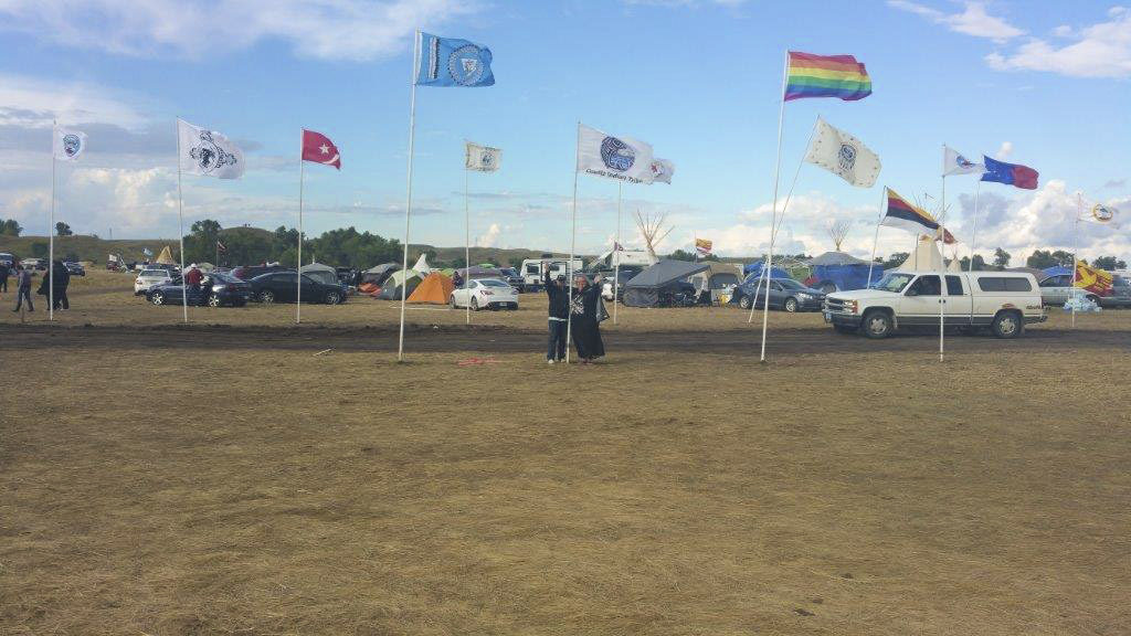 Linda O'Brien, (left) wife of Cowlitz Indian Tribe councilman John O'Brien (not pictured) and Melody Pfeifer, a member of the Cowlitz tribe and the tribe's youth program coordinator, stand under the Cowlitz flag at a gathering of hundreds of native tribes from the United States, Canada and Latin America in North Dakotas to resist the construction of a crude oil pipeline that will traverse four states and go under the Missouri River, a drinking water source for the Standing Rock Sioux Indian Tribe. Photo courtesy of Melody Pfeifer, Cowlitz Indian Tribe