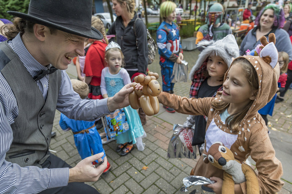 Balloonist Dominic Hunter was on hand Wednesday at the annual Downtown Washougal Pumpkin Harvest Festival. Here, Hunter offers one of his creations to 7-year-old Aubrey Gay of Washougal. Photo by Mike Schultz