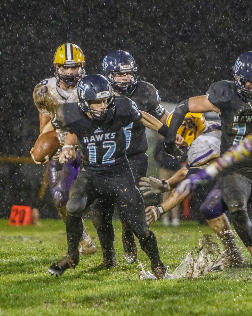 Hockinson quarterback Canon Racanelli (12) runs through the mud for a big gain against Columbia River Friday. Photo by Mike Schultz.