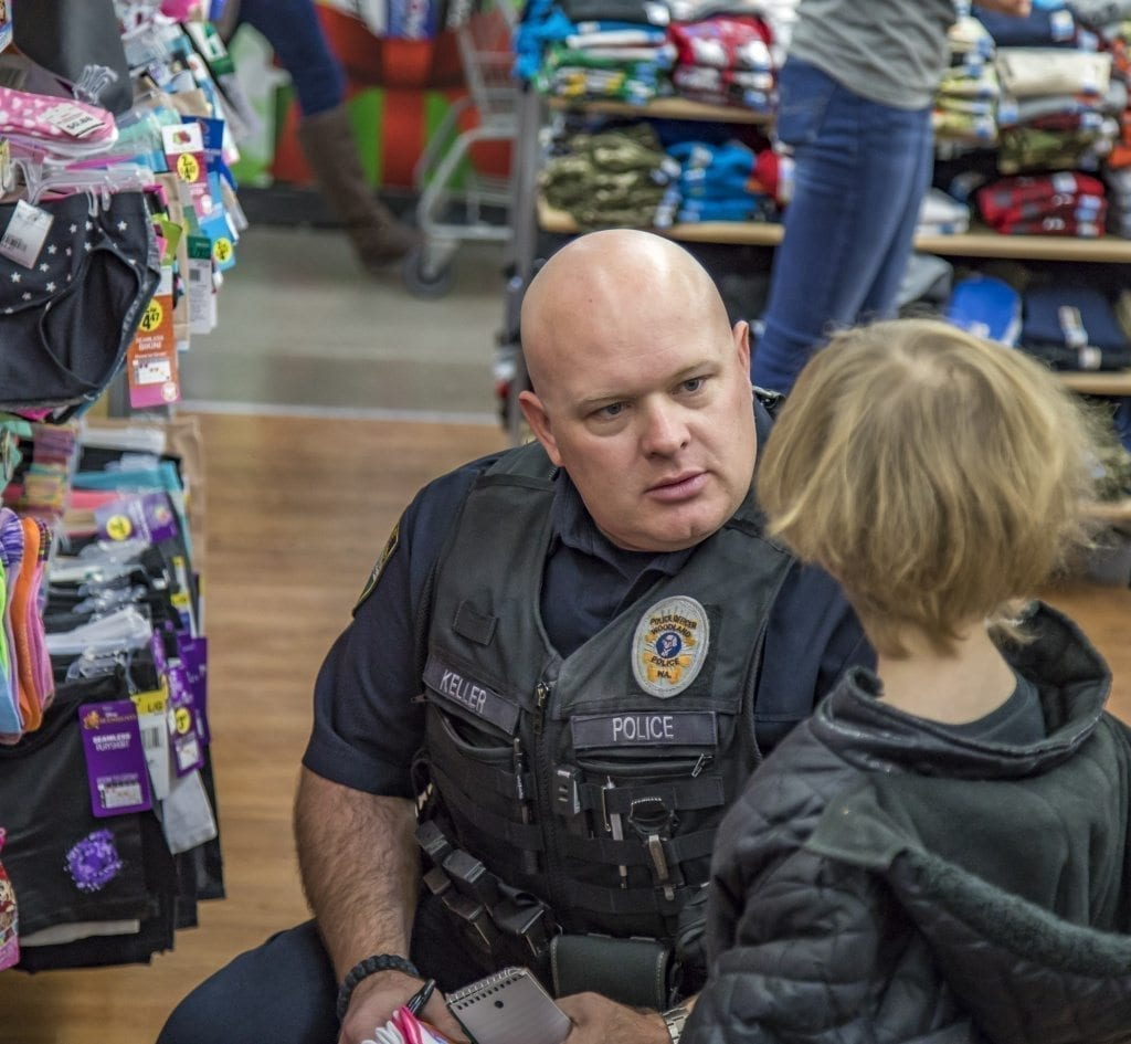 Jim Keller, of the Woodland Police Department, helps this youngster gather his thoughts and implement a strategy at the annual Shop With a Cop event Saturday at the Woodland Walmart. Photo by Mike Schultz