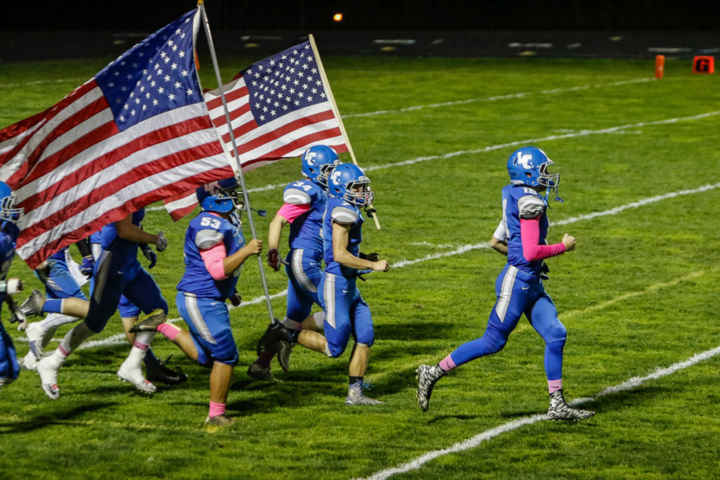 La Center football team charges onto the field before a win against Castle Rock Friday at La Center High School.