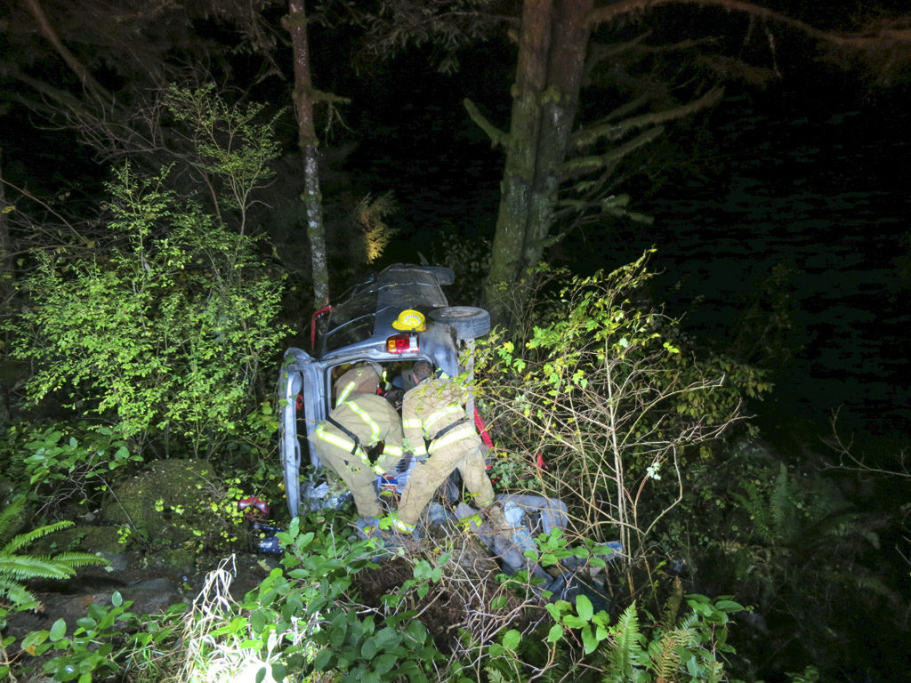 Crews assist the occupants of a vehicle that went over an embankment on NE Lucia Falls Rd.Saturday evening. Photo courtesy of Fire District 3
