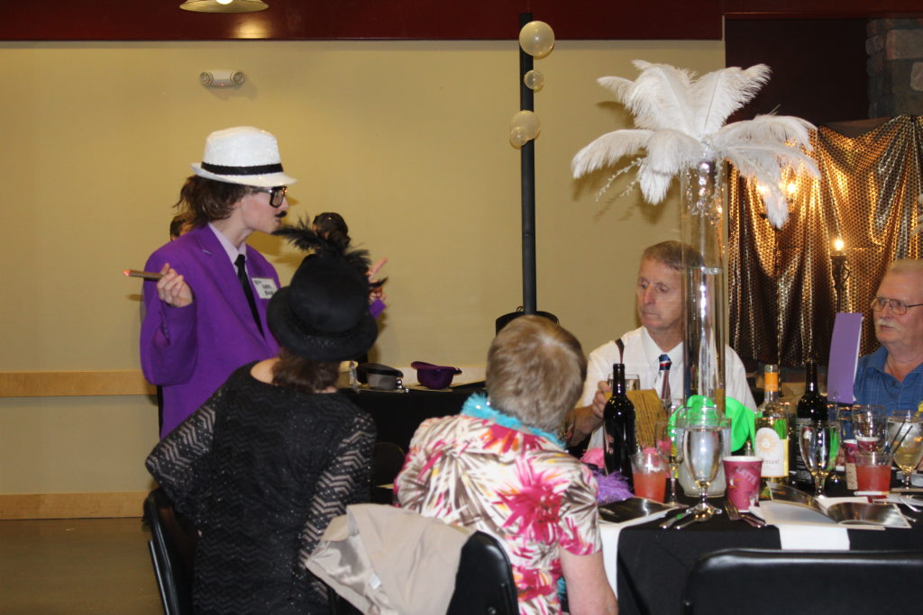 Mafia Don Lou Zar, played by an actress from The Murder Mystery Company of Portland, talks with a group of attendees at the Scare Away Hunger dinner and auction on Saturday night. Everyone in the room later became investigators after someone decided to off Lou. Photo by Joanna Yorke