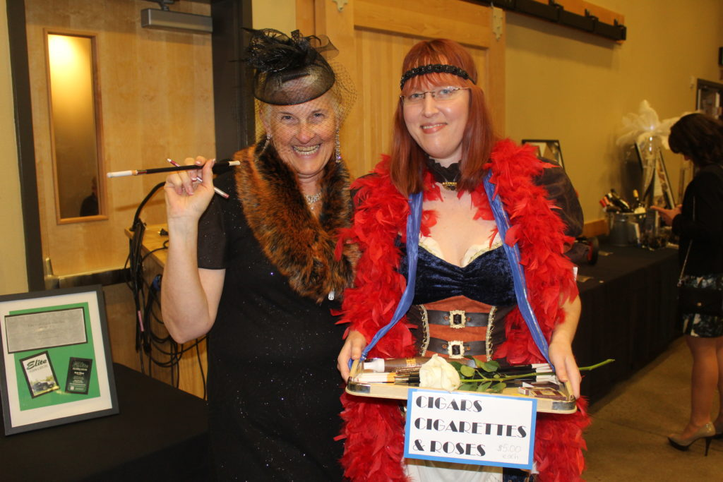 Bev Jones and Heather Steinke, volunteers with the North County Community Food Bank, looked the part as they passed out some accessories — fake cigars and cigarettes, and roses — to help complete attendees' 1920s attire. Photo by Joanna Yorke