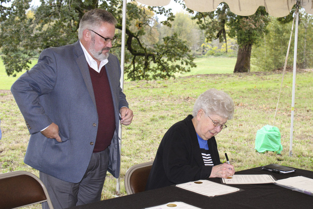 Emma Schmid, matriarch of the Washougal Schmid family, signs a deed to the city for 17.88-acre parcel near the Washougal River that her family has owned since the 1950s. To her left, Washougal Mayor Sean Guard watches the deed signing on Thu., Oct. 6. Photo by Kelly Moyer.