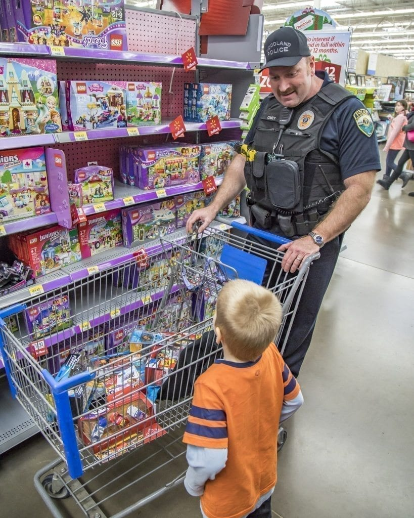 Terry Casey, of the Woodland Police Department, and his youngster still have room to fill in their shopping cart. Photo by Mike Schultz
