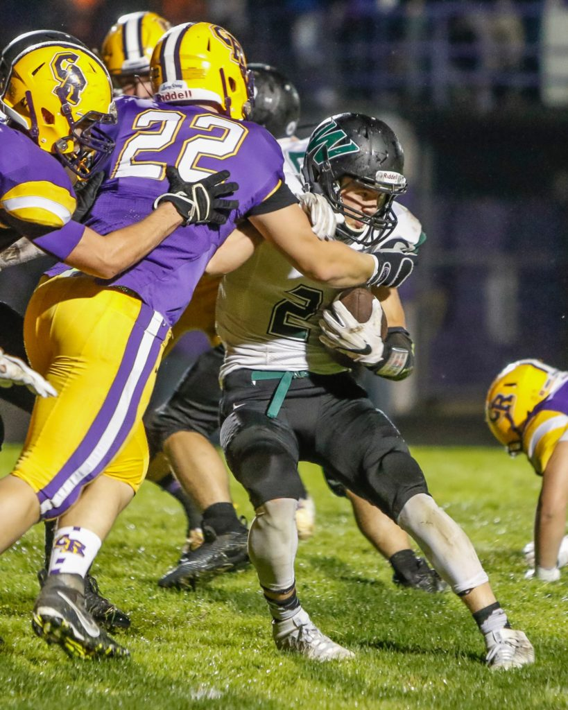 Woodland wide receiver Tyler Flanagan (21) is stopped by Columbia River linebacker Kaleb Haggard (22). Photo by Mike Schultz.