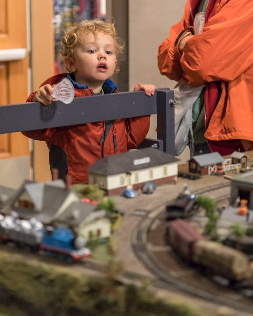 Griffin Mullin (3) of Seattle views a model train set up by the Southwest Washington Model Railroaders at the Vancouver Rotary Foundation Festival of Trees. Photo by Mike Schultz