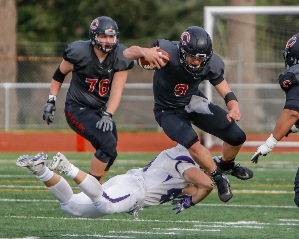 Camas quarterback Jake Colletto (9) jumps over a Sumner defender. Photo by Mike Schultz