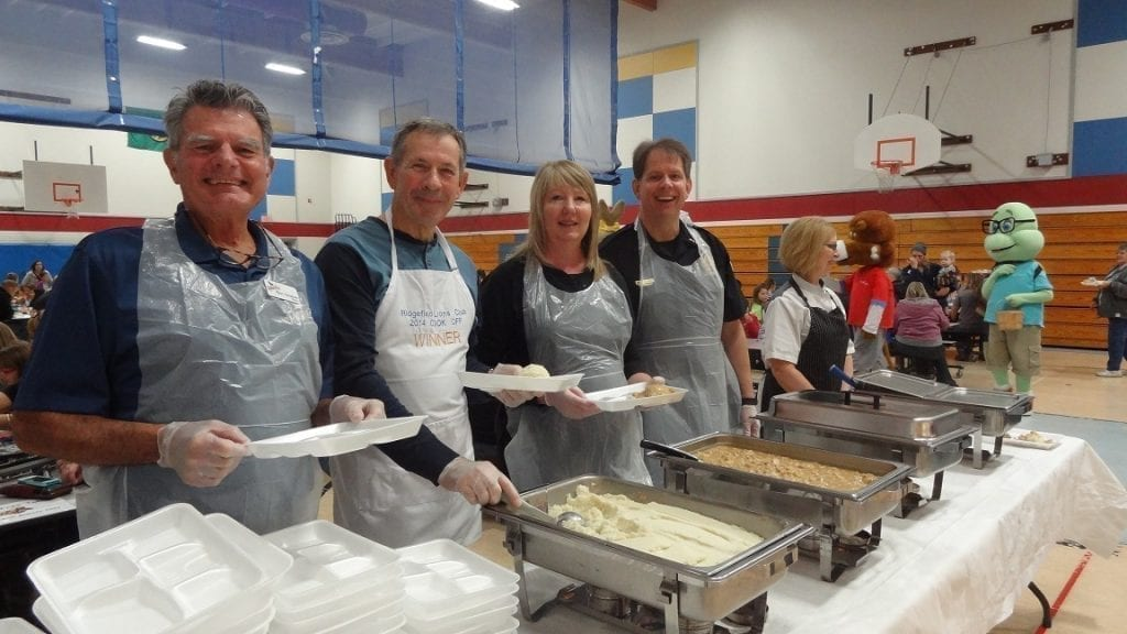 Ridgefield city officials serve up Thanksgiving lunches in Ridgefield Schools. Pictured, from left, are Mayor Ron Onslow, City Councilor Don Stose, Police Department Clerk Sandra Hoots and Police Chief John Brooks. Photo courtesy of Ridgefield School District
