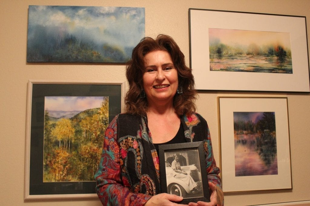 La Center artist Sandra Yorke is pictured here next to a few of her paintings and holding a picture of her late mother, Yvonne Schmidt. Photo by Joanna Yorke