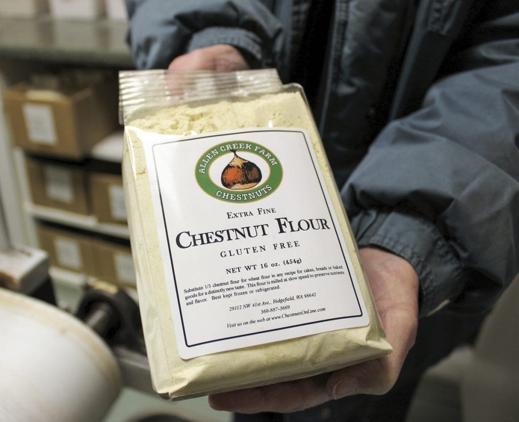 Carolyn Young shows a bag of the sweet-tasting, gluten-free chestnut flour that she and her husband, Ray Young (not pictured) grow and mill at Allen Creek Farm in Ridgefield. Photo by Kelly Moyer