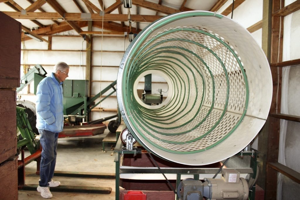 Instead of buying an expensive piece of processing equipment, Ray Young (left) and Carolyn Young (not pictured), owners of Allen Creek chestnut farm in Ridgefield, made this ingenious chestnut sorter to separate the nuts into batches of small, which are milled into chestnut flour, medium, large and extra-large. The hoses keep the chestnuts moving through the spiraling sorter and the holes sort them into their size-specific bins below. Photo by Kelly Moyer