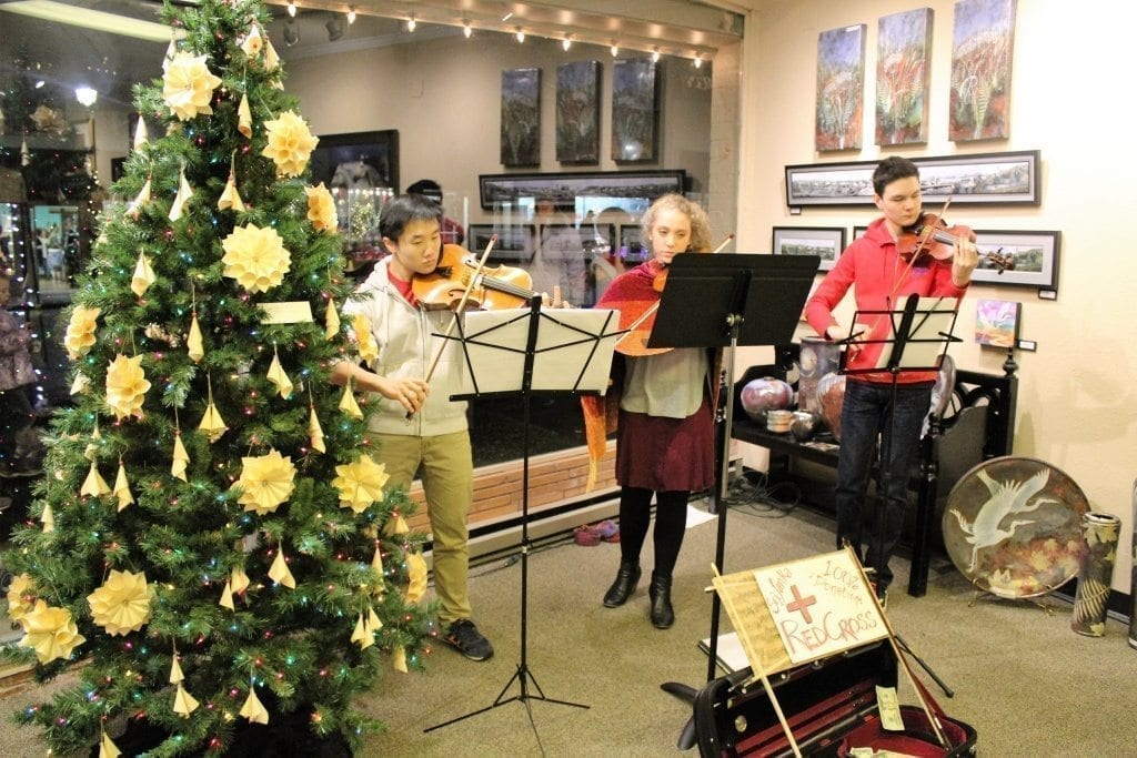 Camas students (from left to right) Jason Kim, 18, Sophia Hansen, 15, and Aaron Greene, 15, perform at the Camas Gallery in downtown Camas on Fri., Dec. 2, for the Camas Hometown Holidays celebration. The three teens are all members of the Portland Youth Philharmonic. Photo by Kelly Moyer