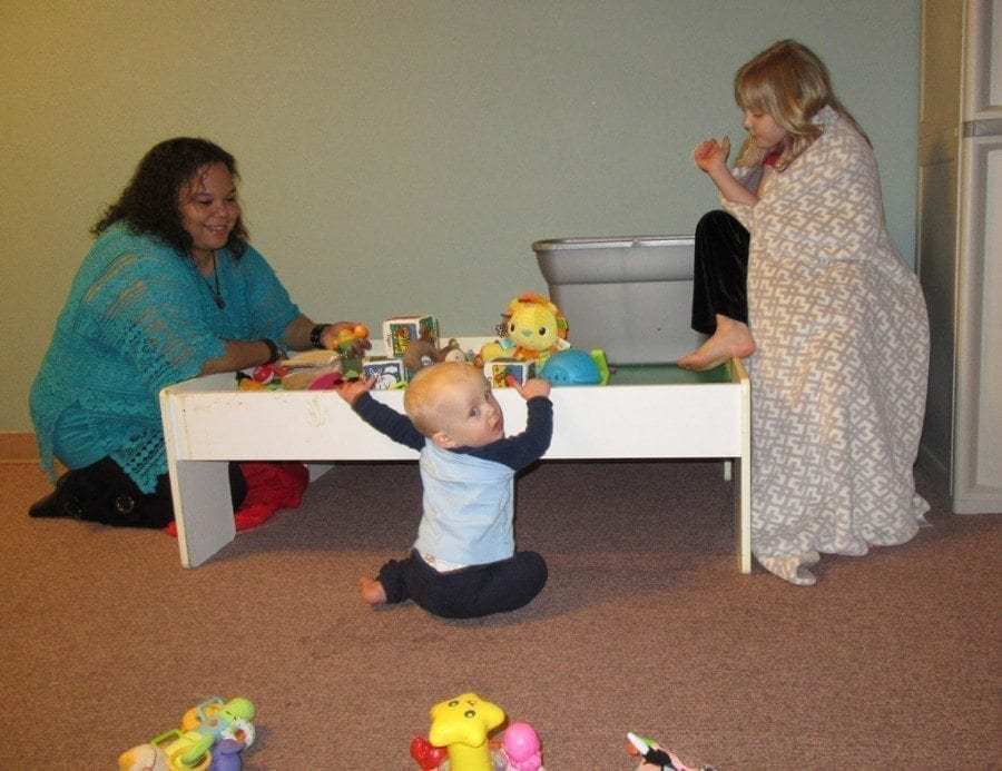 Tamicka Fellows, her husband, and their three children live on-site at Mom's Place Maternity, currently with three women and their six children, aged nine months to six years. Here Fellows plays with residents Jaxson and his sister Kadence. Photo courtesy of Carolyn Schultz-Rathbun