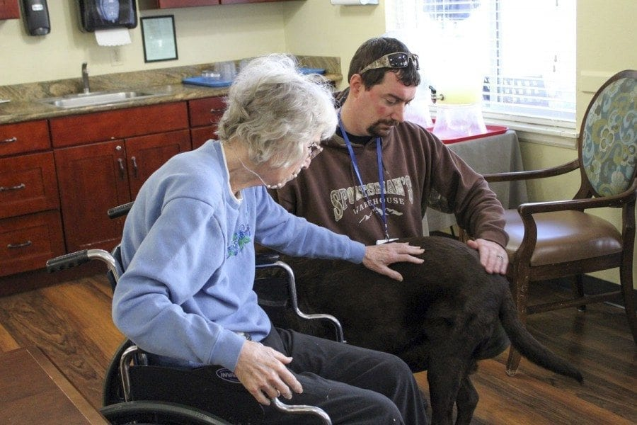 Mike Campbell (right) and Jake (the dog) visit with an area resident as part of the Furry Friends Pet Therapy Program. Photo courtesy of Diane Stevens