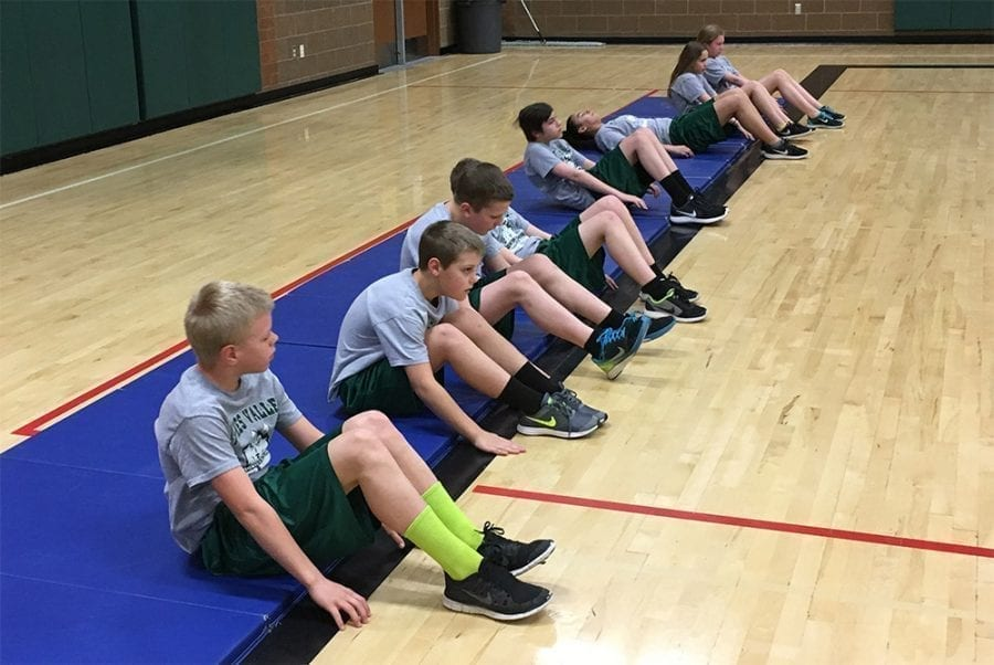 "Battle Ground Public Schools' sixth graders Jaden Tapani, Thomas Parker, Marty Bergman, Cody Thompson, Ellie Lazaroti and Katelyn Pattison perform the ""curl-up"" test during one of their fitness classes. Photo courtesy of Battle Ground Public Schools"