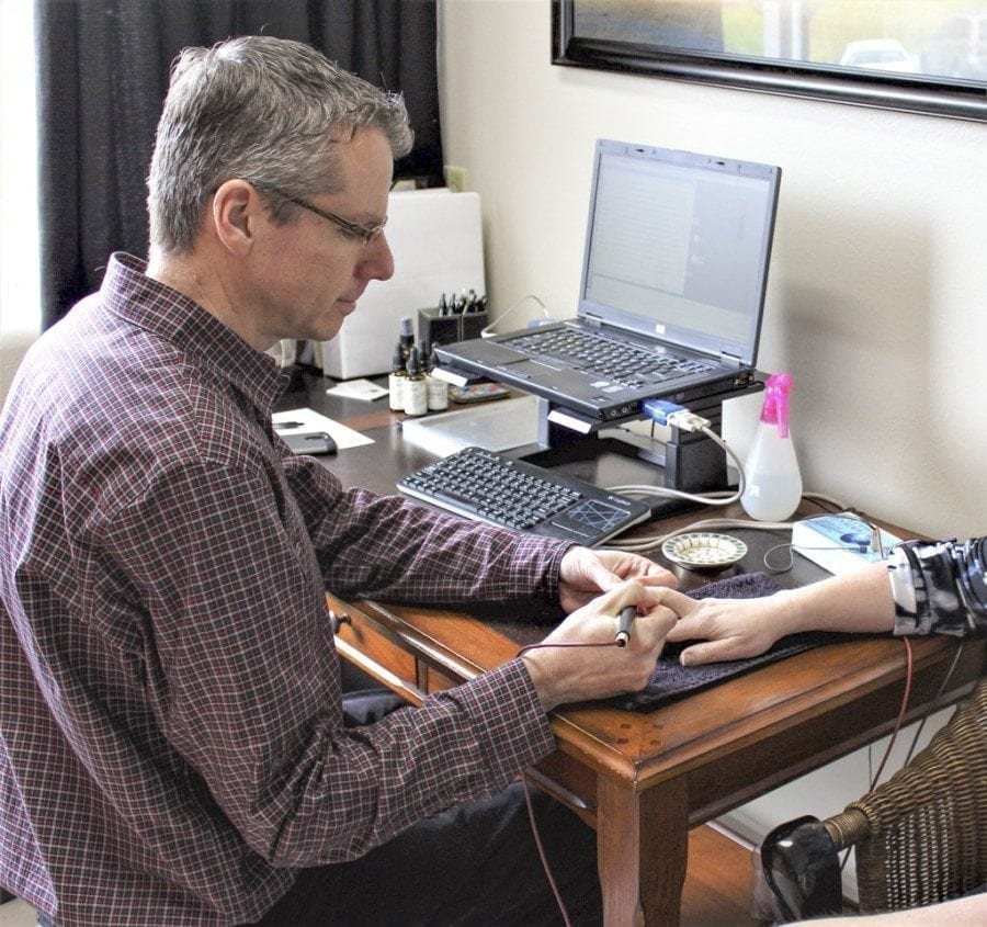 Timothy Lightfoot, an electrodermal screening therapist at Peace Yourself Together, a new holistic healing center located at 506 N.E. Everett St., in Camas, demonstrates the bio-energetic screening equipment he uses at his practice. Photo by Kelly Moyer