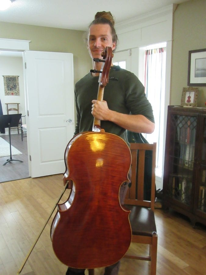 Portland cellist Tim Berte-Renou is shown here with Mark Moreland's newest cello. Photo courtesy of Carolyn Schultz-Rathbun