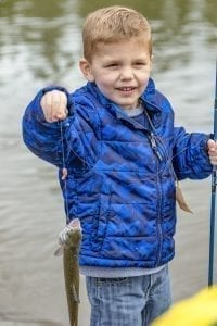 Easton Wills, age 5 of Vancouver, was one of an estimated 3,200 children who participated in the Klineline Kids Fishing event held this weekend at Salmon Creek Park/Klineline Pond in Vancouver. Here, he shows off the catch he made Saturday. Photo by Mike Schultz