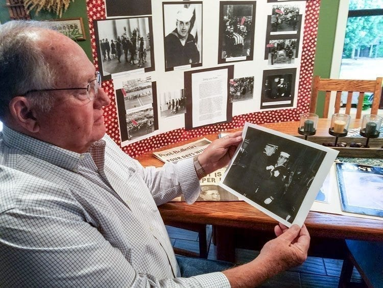 """""""Bud"""" Barnum looks at a photograph of him receiving an Army Commendation Medal after his service with the honor guard detail that buried President John F. Kennedy. Barnum was in the U.S. Coast Guard. Photo by Paul Valencia"""