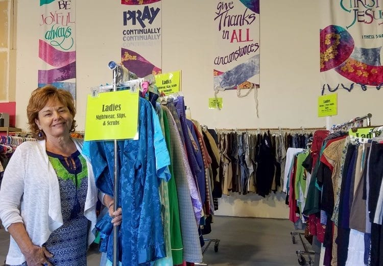 Rev. Denise Currie, the executive director of The Giving Closet, stands beside some of the store's inventory. All items are free for people in need. Photo by Paul Valencia
