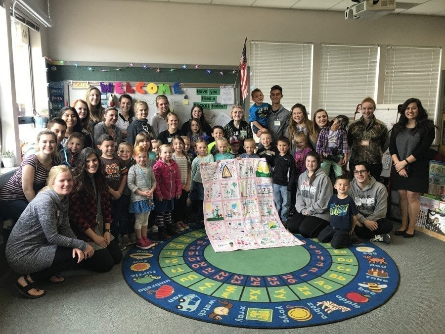 Students in the Older-Younger kindergarten program in the Battle Ground School District pose with a special quilt they created. Photo courtesy of Battle Ground School District