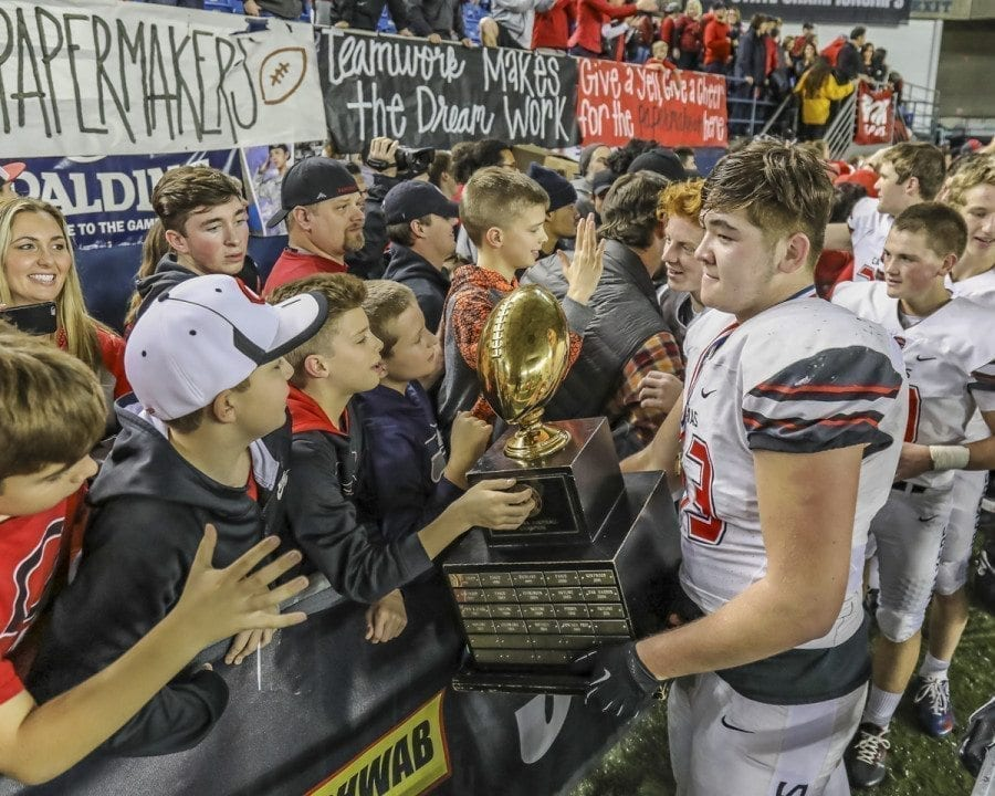 Camas football player Marshall McIvor shares the state championship trophy with some of the team's fans after the Papermakers won the 4A title. Photo by Mike Schultz