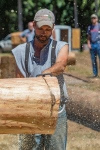 Greg Brown uses his modified saw to cut through a log during the Amboy Territorial Days logging competition Saturday. Photo by Mike Schultz