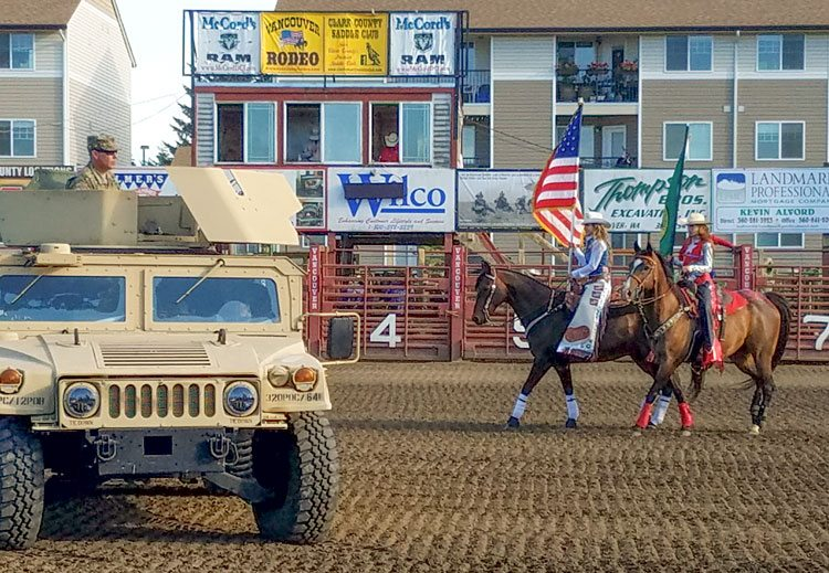 Two riders bring in flags near a U.S. Army vehicle at the start of a swearing in ceremony for local recruits Monday at the Vancouver Rodeo. Photo by Paul Valencia
