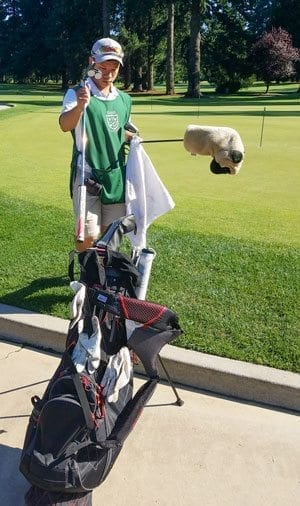 Zach Peros, a recent Skyview High School graduate, cleans clubs prior to a round as part of his duties as a caddy at Royal Oaks Country Club. His work as a caddy, as well as his academics and character, landed him a four-year college scholarship. Photo by Paul Valencia
