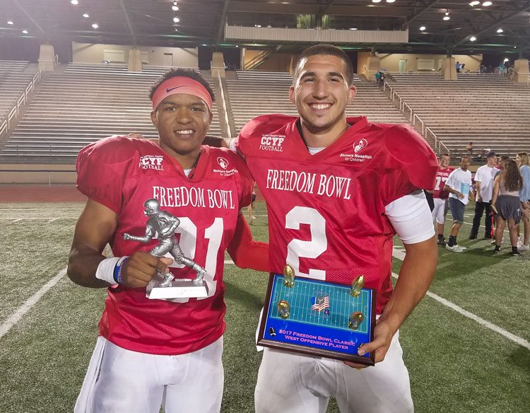 Jeremiah Wright of Skyview (left) took home the overall MVP trophy of the Freedom Bowl Classic. Jordan Hickman of Hudson's Bay was the offensive player of the game for the victorious West team. Photo by Paul Valencia