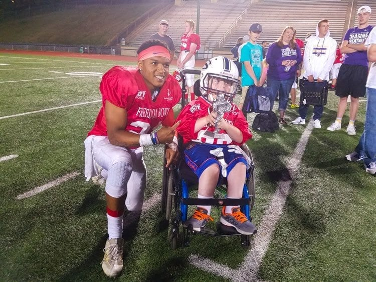 West co-captain Andrew Norton got a moment to hold Jeremiah Wright's MVP trophy after Saturday's game at McKenzie Stadium. The Freedom Bowl Classic raises funds for Shriners Hospitals for Children. Photo by Paul Valencia