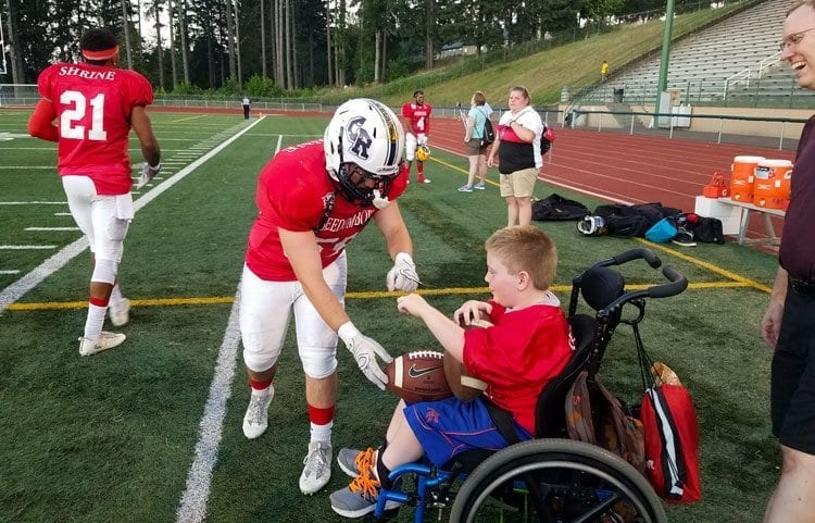 Ryan Hull of Skyview gives a fist-pump to Andrew Norton, a co-captain of the West team in the Freedom Bowl Classic, a game that raises funds for Shriners Hospitals for Children. Photo by Paul Valencia