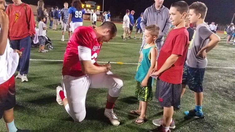 Jordan Hickman of Hudson's Bay signs autographs after leading the West All-Stars to a 38-23 victory at Saturday's Freedom Bowl Classic. Photo by Paul Valencia