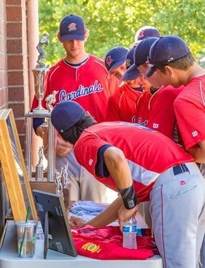 Players from this year's Vancouver Cardinals gather around the table to check out the collection of memorabilia from the 1987 team that finished second in the American Legion World Series. Photo by Mike Schultz