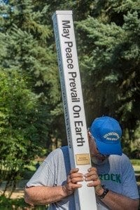 """Vancouver Sunrise Rotary Member Bob Ives holds the Peace Pole that he and fellow club members installed at Orchards Park Saturday. The Peace Pole displays the prayer """"May Peace Prevail on Earth'' in four languages. Photo by Mike Schultz"""